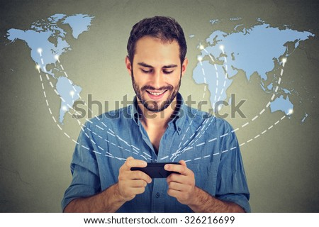Modern communication technology mobile phone high tech, web connection concept. Happy business man holding smartphone connected browsing internet worldwide world map background.  - stock photo