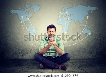 Modern communication technology mobile phone high tech, web connection concept. Happy man sitting on a floor using smartphone connected browsing internet worldwide world map background.