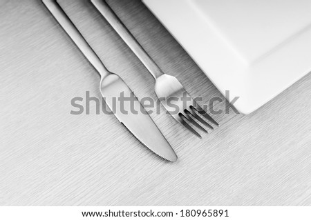 Modern composition of knife, fork and white plate on wooden table in black and white - stock photo