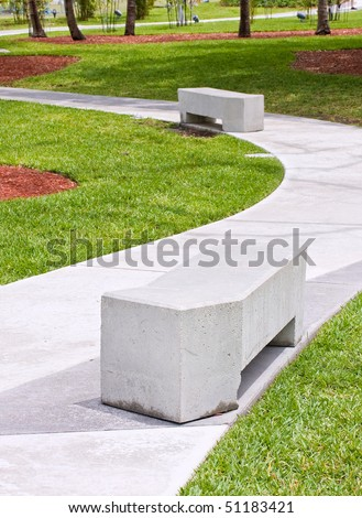 Modern concrete benches and path in a public park with green grass and trees on a beautiful spring day