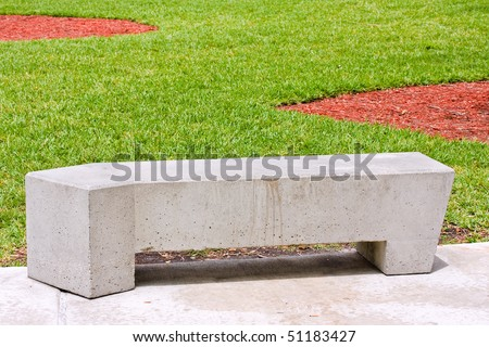 Modern concrete benches and path in a public park with green grass on a beautiful spring day
