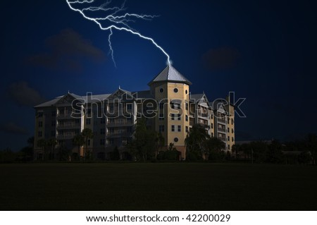 Modern Condominium being struck by lightning on top of the tower - stock photo