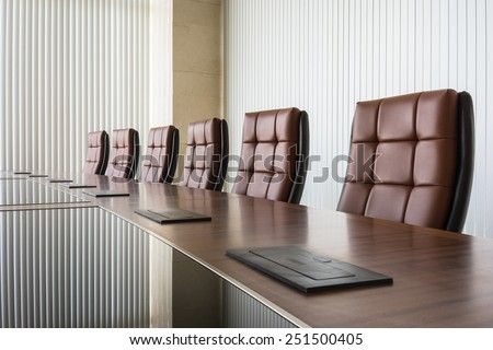 Modern conference room with brown leather chair and glass surface table - stock photo