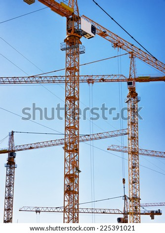 modern construction cranes in front of blue sky