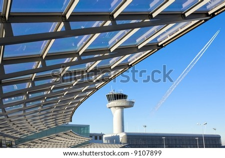 modern construction with airport control tower  and airplane line in blue sky - stock photo