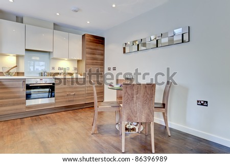 Modern contemporary breakfast kitchen with built in appliances, table and chairs - stock photo
