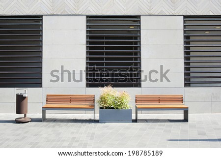 Modern contemporary fasade with windows and two wooden benches - stock photo