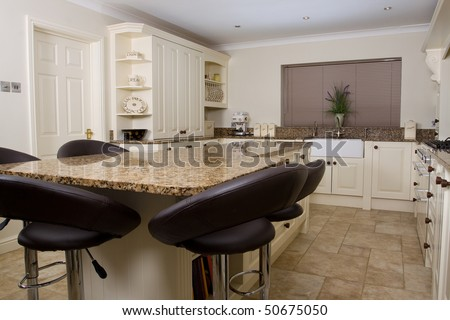 Modern contemporary kitchen interior with granite worktop and cream units and black stools - stock photo