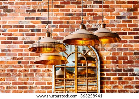 modern copper lights against a brick wall - stock photo