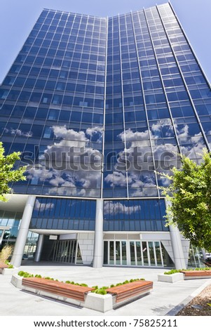 Modern Corporate Building with sky and clouds reflecting - stock photo