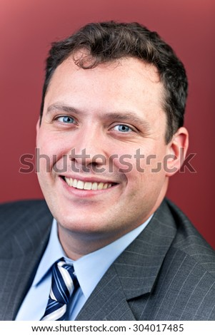 Modern corporate headshot style portrait of a cheerful business man isolated over a red background.  - stock photo