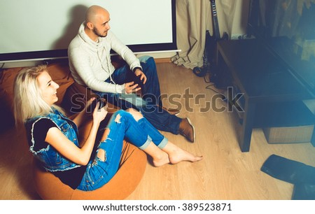 Modern couple in casual clothes having fun and playing computer games. concept of leisure entertainment and fun - stock photo