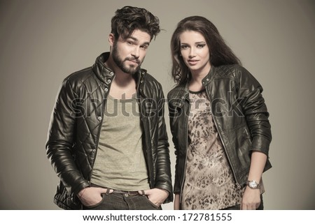 modern couple in leather clothes standing next to each other and looking at the camera in studio