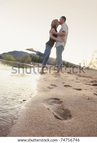 modern couple kissing each other on beach with footprints in sand