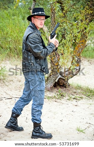 modern cowboy standing on sand, trees on background - stock photo