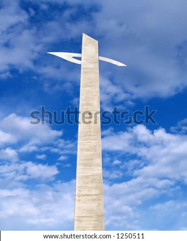 Modern cross and cloudy sky
