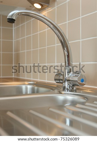 Modern curved mixer tap - stock photo