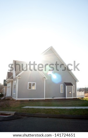 Modern custom built house newly constructed in a residential neighborhood with strong lens flare.  Gas fireplace bump out visible on the side. - stock photo