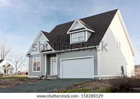 Modern custom built house newly constructed with a two car garage in a residential neighborhood. - stock photo
