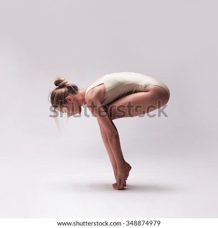 Modern dancer set. Young beautiful modern dancer in sitting pose, wearing beige swimsuit posing on a grey gradient studio background - stock photo