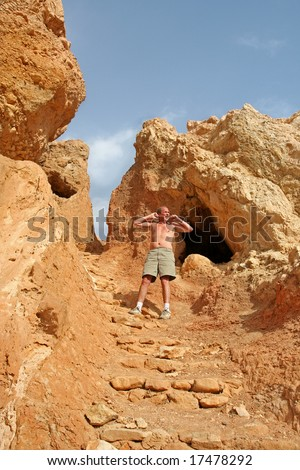 Modern Day Caveman emerges from Cave and stretches with a yawn. Taken in the Atlas Mountains of North Africa - stock photo