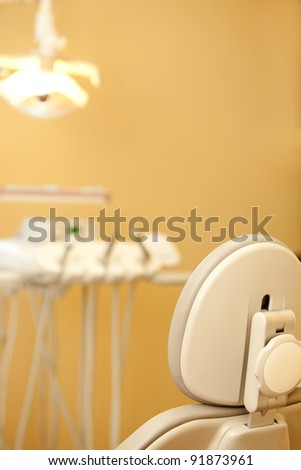 Modern Dental Chair with Tray and Light in the Background - stock photo