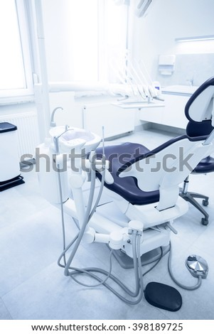 Modern dental practice. Dental chair and other accessories used by dentists in blue, medic light