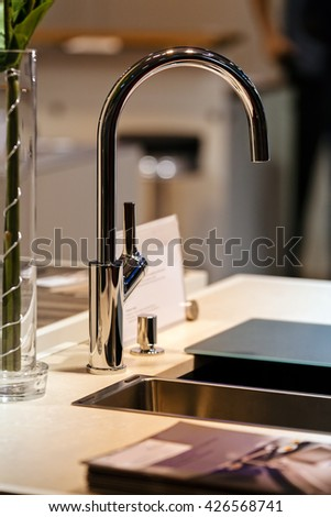 modern design of chrome faucet for sink;  note shallow depth of field