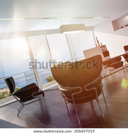 Modern design office interior with comfortable chairs around a central table and easel in the corner with floor-to-ceiling windows overlooking the sea - stock photo