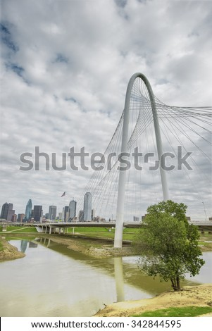 Modern design suspension Margaret Hunt Hill Bridge and the Dallas skyline in the distant background - stock photo