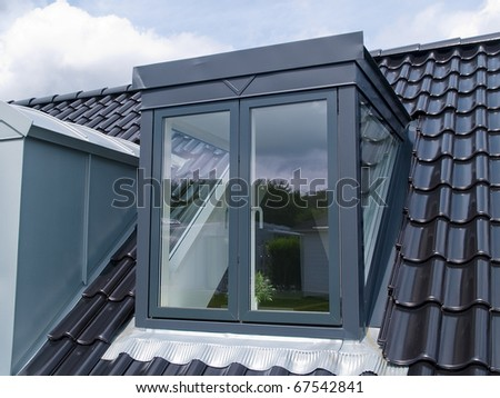 Modern design vertical roof window with black tiles - stock photo