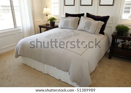 Modern designer bedroom with decorative duvet and pillows. - stock photo