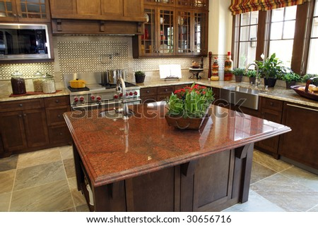 Modern designer kitchen with brown tiles and a granite island. - stock photo