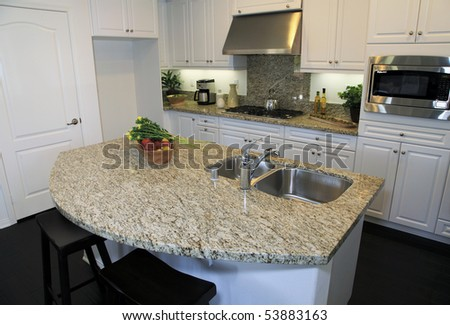 Modern designer kitchen with stainless steel appliances and a granite island. - stock photo