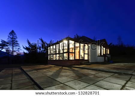 Modern detached house photographed at blue hour, just after sunset. - stock photo