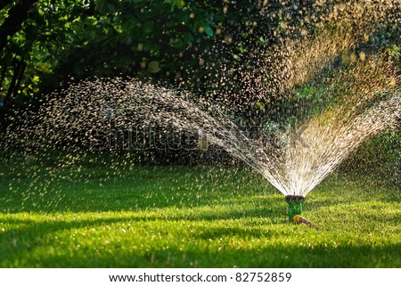 Modern device of irrigation garden. Irrigation system - technique of watering in the garden. Lawn sprinkler spraying water over green grass. - stock photo