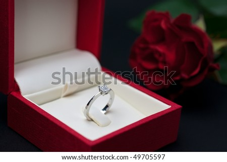 Modern diamond engagement ring in red jewellery box on black background (soft focus) - stock photo