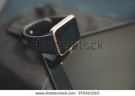 Modern digital accessory - fashionable smart wrist watch on talbet pc and travel bag. This gadgets let you always stay connected to social media, email, internet. Horizontal orientation, fading colors - stock photo