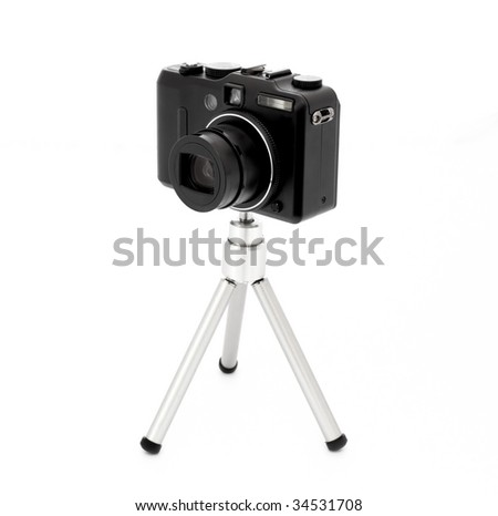 Modern digital camera with tripod. Isolated on white. - stock photo
