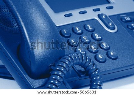 Modern Digital Phone. Shallow depth of field. Focus on cord. Visible texture of plastic. - stock photo