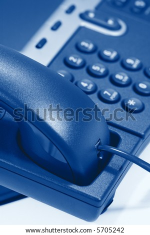 Modern Digital Phone. Shallow depth of field. Focus on handset and cord. Visible texture of plastic. - stock photo
