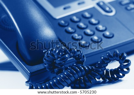 Modern Digital Phone. Very shallow depth of field. Focus on cord. Visible texture of plastic. - stock photo