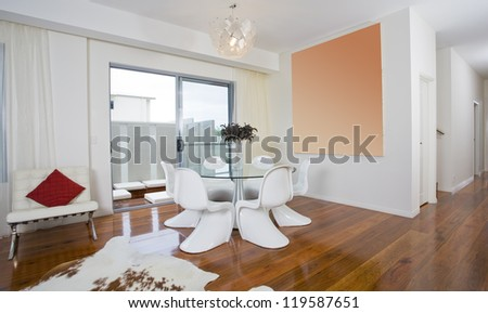 Modern dining area with round table and funky chairs - stock photo