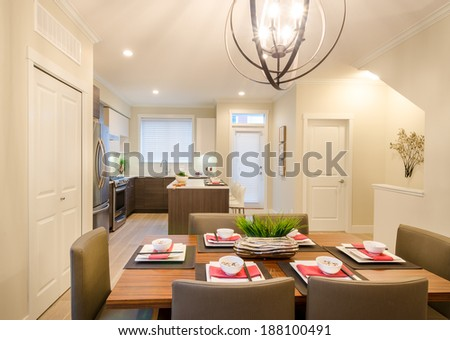 Modern dining room table with plates and bowls in a house, hotel with a kitchen in the background. Interior design. - stock photo