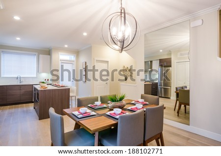 Modern dining room with a kitchen, table, and mirror. Interior design. - stock photo