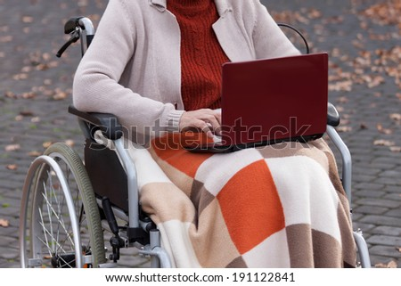 Modern disabled lady on wheelchair using netbook - stock photo