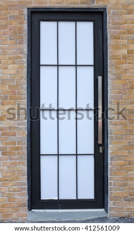 Modern door with grating in a brick wall  - stock photo