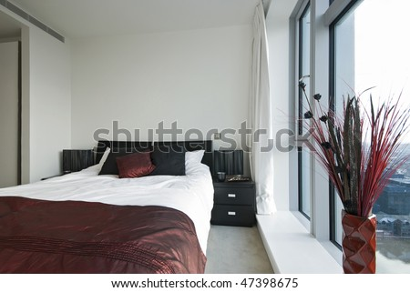 Modern double bedroom with built in wardrobe and floor to ceiling windows - stock photo
