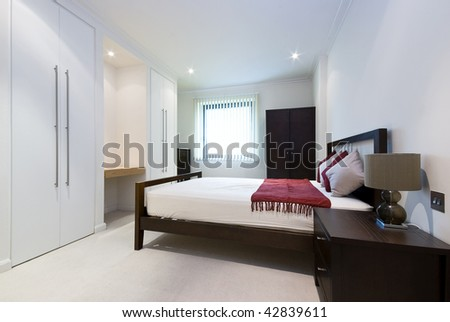 modern double bedroom with king size bed, built in wardrobes and bedside tables - stock photo