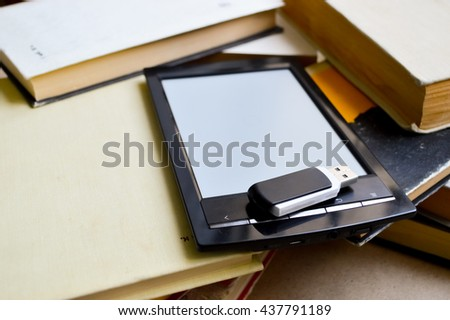modern ebook reader stacked against pile of old books.modern technology against the books - stock photo